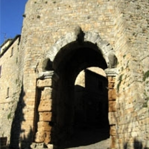 Volterra city gate with Etruscan sculptures Italy
